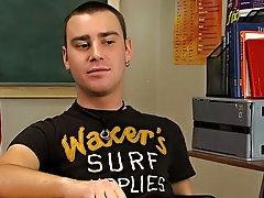Young brunette twink Justin Giles sits at a desk in a classroom and the man behind the camera asks him questions about his experience in porn, his sex